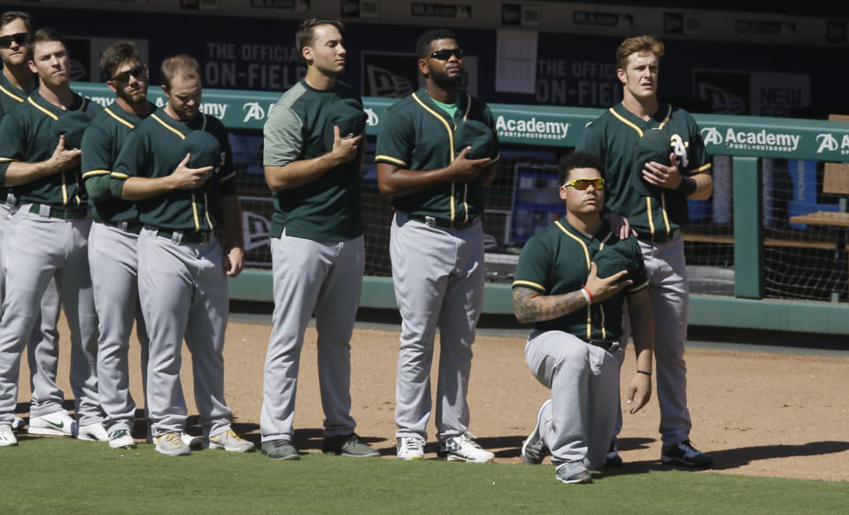 Oakland Athletics catcher Bruce Maxwell takes a knee next to teammate Mark Canha (R) during the national anthem before a baseball game against the Texas Rangers in Arlington, Texas, Sunday, Oct. 1, 2017. (AP Photo/LM Otero)
