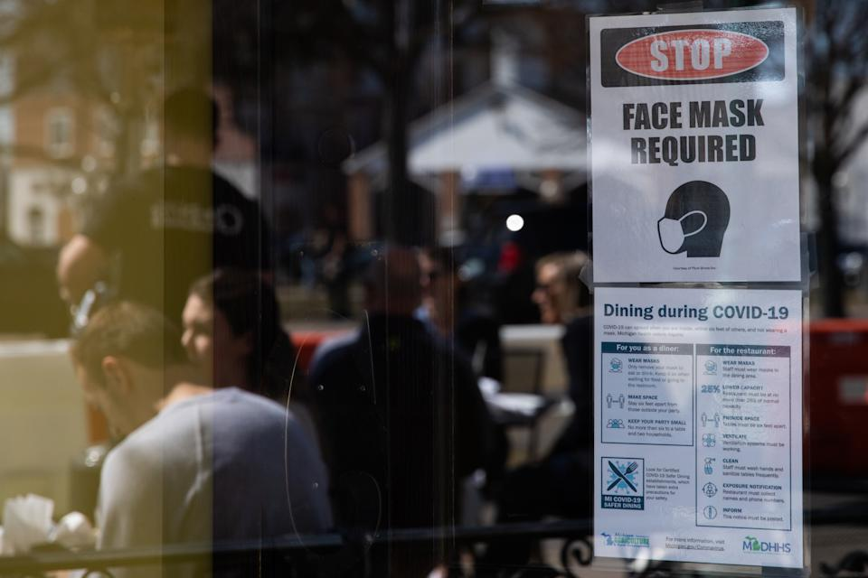 A sign requiring face masks and Covid-19 protocols at a restaurant in Plymouth, Michigan, U.S., on Sunday, March 21, 2021. (Emily Elconin/Bloomberg via Getty Images)