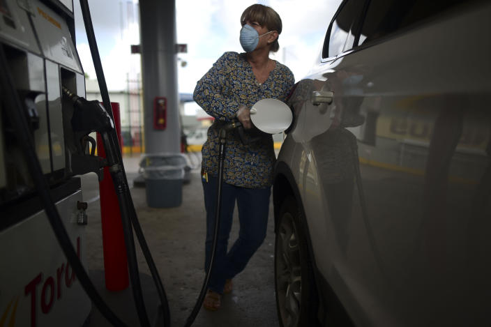 A woman wears a face mask and gloves at the gas station during a government ordered quarantine aimed at curbing the spread of the new coronavirus, that is shuttering all non-essential businesses for two weeks in San Juan, Puerto Rico, Thursday, March 19, 2020. (AP Photo/Carlos Giusti)