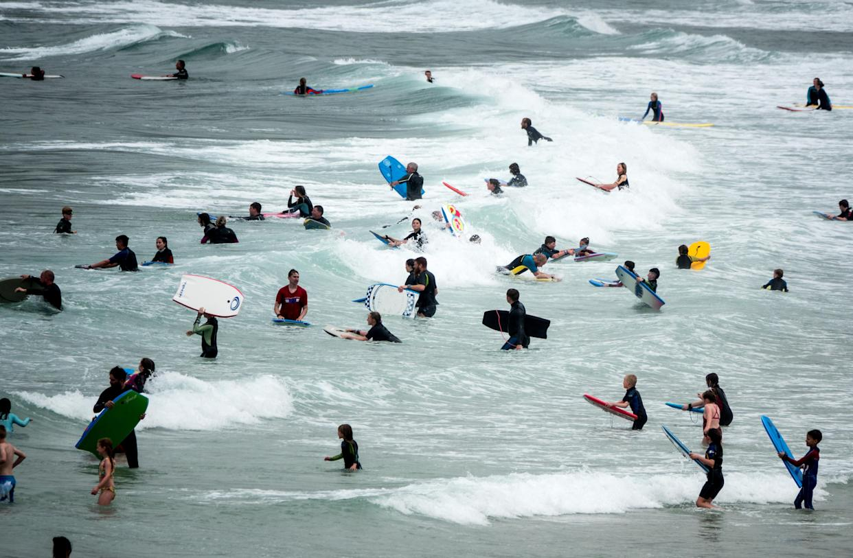SENNEN COVE, ENGLAND - AUGUST 01: People crowd into the sea to swim, surf and bodyboard at Sennen Cove on August 1, 2021 in Cornwall, England. With international travel restrictions remaining likely for this summer at least, many parts of the UK are set to be very popular with holidaymakers opting to have domestic holiday or a so called staycation within the UK. (Photo by Matt Cardy/Getty Images)