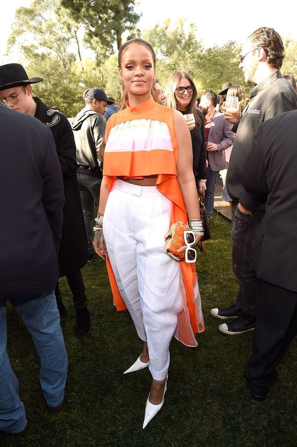 <p>In an orange crop top and white trousers by Delpozo with a tangerine-colored clutch and white pointy-toed pumps. </p>