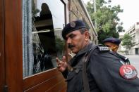 Police officers gather at the damaged security post of the Pakistan Stock Exchange building after an attack in Karachi