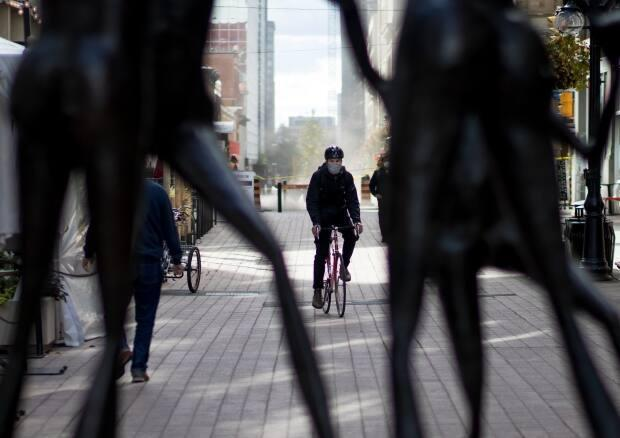 A cyclist wearing a mask is framed by a Sparks Street statue in late September 2021, during the fourth wave of the COVID-19 pandemic. On Saturday, public health officials in the nation's capital reported 62 new cases of the illness. (Trevor Pritchard/CBC - image credit)