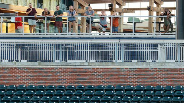 PHOTO: Guests of the Omni Hotel look on from the swimming pool area as they watch Atlanta Braves in their first intrasquad game of summer workouts at Truist Park, on July 13, 2020, in Atlanta. (Kevin C. Cox/Getty Images)