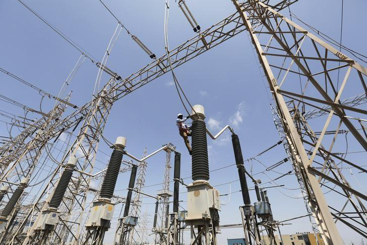 A technician repairs power supply lines at a power plant of Adani Power at Mundra Port in the western Indian state of Gujarat