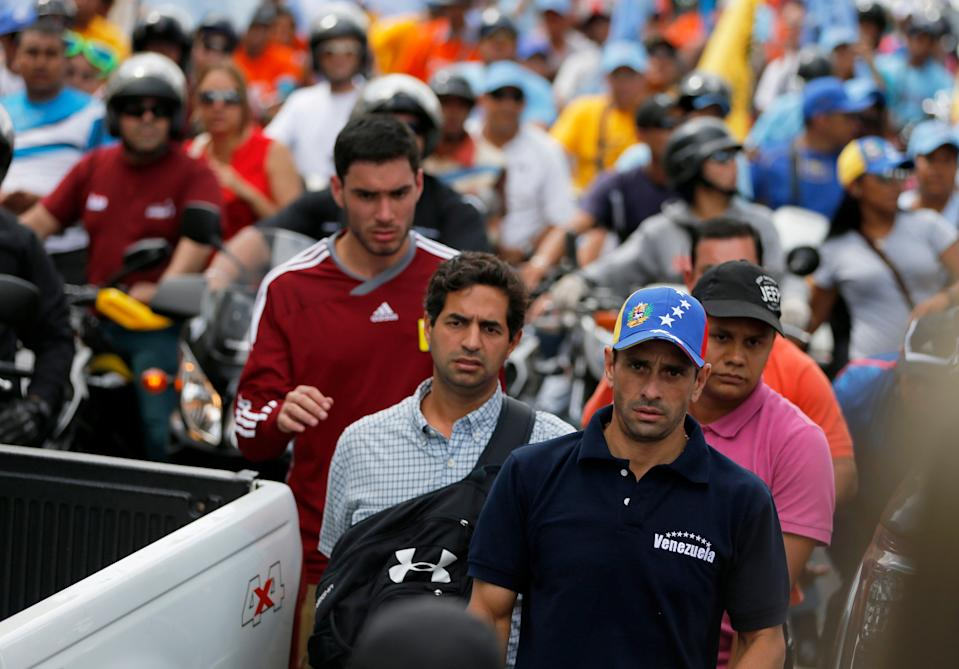 In this Sunday, Dec. 1, 2013 photo, opposition leader Henrique Capriles is followed by bodyguards and supporters during a political rally in Caracas, Venezuela. The visibly thinner and exhausted Capriles is accompanied by just a handful of journalists at what was supposed to be one of the final, electrifying opposition rallies ahead of this weekend's mayoral elections. (AP Photo/Fernando Llano)