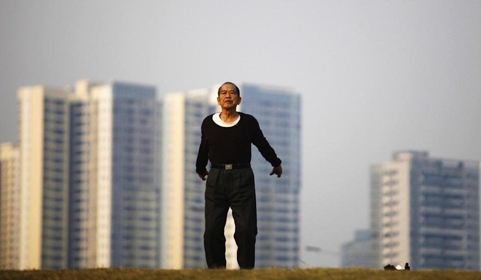 A man does morning exercises in park near a new residential compound in Guangdong's capital, Guangzhou. Photo: Reuters