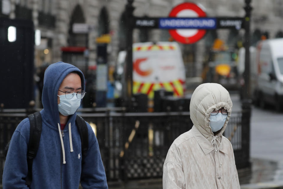 Pedestrians wear face masks as they walk at Piccadilly Circus main tourist destination in central London, as the public are asked to take precautions to protect themselves from the COVID-19 Coronavirus outbreak,  Thursday, March 5, 2020.(AP Photo/Frank Augstein)