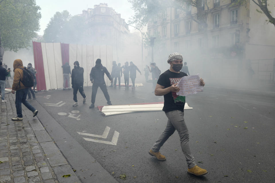 Youths set up a barricade during a banned protest in support of Palestinians in the Gaza Strip, in Paris, Saturday, May, 15, 2021. Marches in support of Palestinians in the Gaza Strip were being held Saturday in a dozen French cities, but the focus was on Paris, where riot police got ready as organizers said they would defy a ban on the protest. (AP Photo/Rafael Yaghbozadeh)