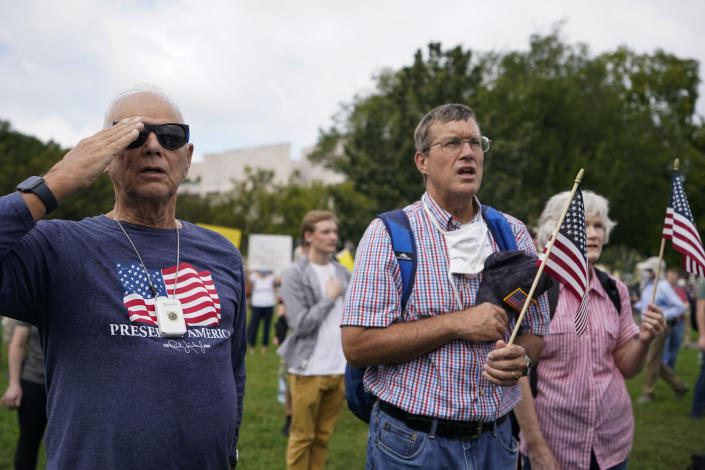 """People stand as the national anthem plays during a rally near the U.S. Capitol in Washington, Saturday, Sept. 18, 2021. The rally was planned by allies of former President Donald Trump and aimed at supporting the so-called """"political prisoners"""" of the Jan. 6 insurrection at the U.S. Capitol. (AP Photo/Brynn Anderson)"""