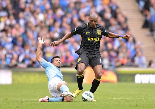 Manchester City's Sergio Aguero and Wigan Athletic's Emmerson Boyce (right) battle for the ball
