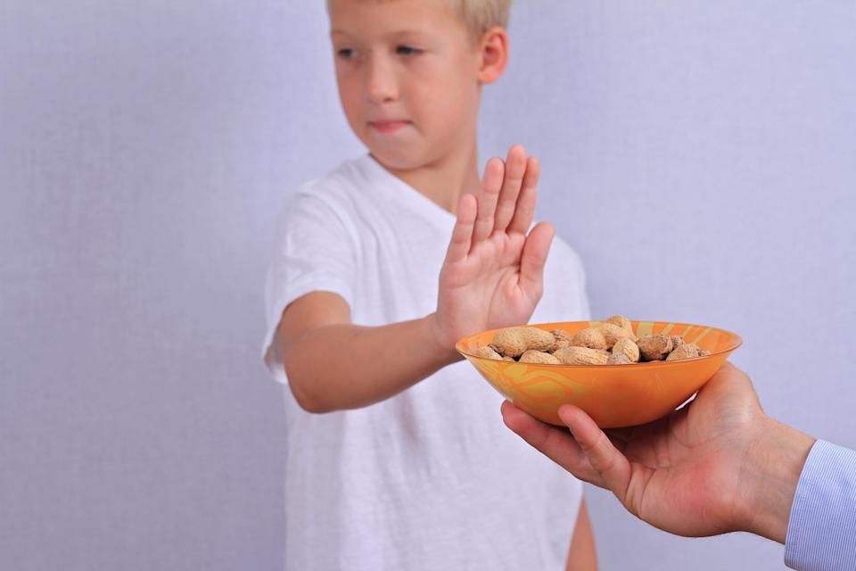 Boy sticking his hand out refusing a bowl of peanuts.