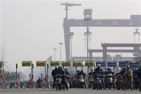 Workers ride motorcycles and bicycles after their shifts, at an entrance of the Rongsheng Heavy Industries shipyard in Nantong, Jiangsu province, in this December 4, 2013 file photo. REUTERS/Aly Song/Files