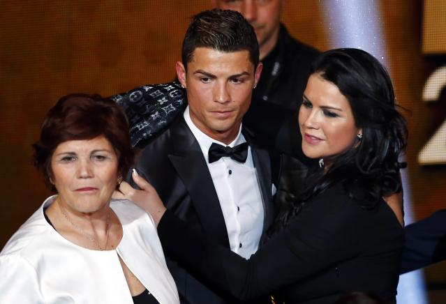 Portugal's Cristiano Ronaldo poses with his mother Dolores Aveiro (L) and sister Katia Aveiro after being awarded the FIFA Ballon d'Or 2013 in Zurich January 13, 2014. Portugal and Real Madrid forward Cristiano Ronaldo was named the world's best footballer for the second time on Monday, preventing his great rival Lionel Messi from winning the award for a fifth year in a row. REUTERS/Arnd Wiegmann (SWITZERLAND - Tags: SPORT SOCCER)