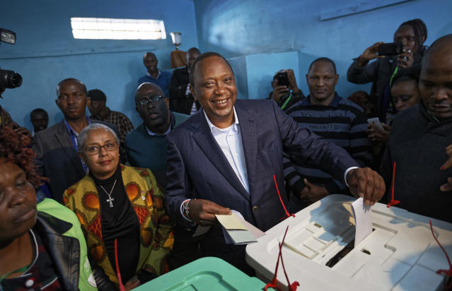 <p>Kenya's President Uhuru Kenyatta casts his vote, accompanied by his wife Margaret, center-left, in Gatundu, north of Nairobi, in Kenya Tuesday, Aug. 8, 2017. (Photo: Ben Curtis/AP) </p>