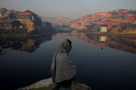 FILE PHOTO: A Rohingya refugee stands next to a pond in the early morning at the Balukhali refugee camp near Cox's Bazar, Bangladesh December 26, 2017. REUTERS/Marko Djurica/File Photo