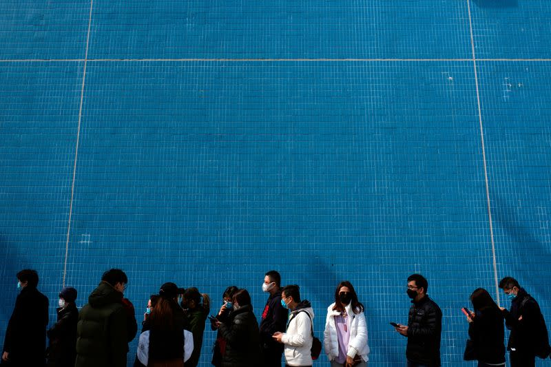 FILE PHOTO: Customers queue to buy face masks to protect themselves from an outbreak of a new coronavirus in Hong Kong