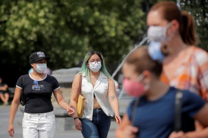 FILE PHOTO: People wear masks, as cases of the infectious Delta variant of COVID-19 continue to rise, in Washington Square Park in New York