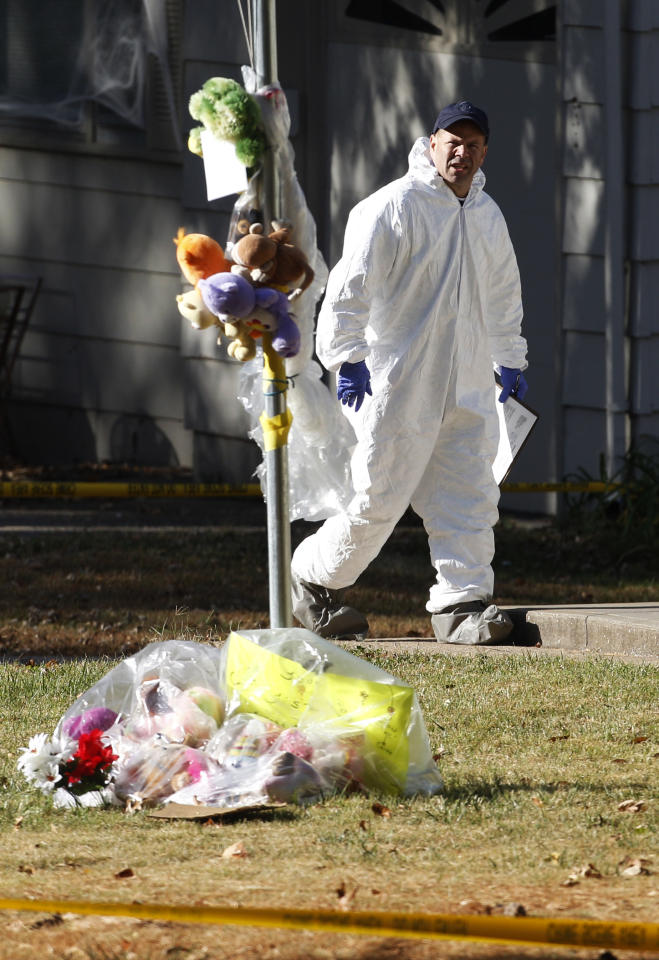 An investigator walks past a memorial at missing baby Lisa Irwin's home in Kansas City, Mo., Wednesday, Oct. 19, 2011. (AP Photo/Orlin Wagner)