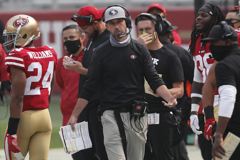 Kyle Shanahan, in a black long-sleeve shirt, holds his hand in despair.