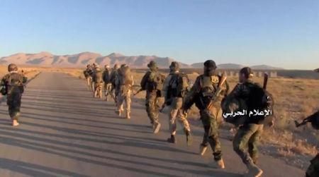A still image taken on August 19, 2017 from a footage of Hezbollah military handout shows Hezbollah fighters walk at western Qalamoun, Syria. Hezbollah Military Handout via Reuters TV.