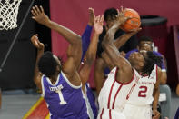 Oklahoma forward Victor Iwuakor, right, goes up for a shot while defended by Kansas State forward Kaosi Ezeagu (1) and guard Selton Miguel, center, during the first half of an NCAA college basketball game Tuesday, Jan. 19, 2021, in Norman, Okla. (AP Photo/Sue Ogrocki)