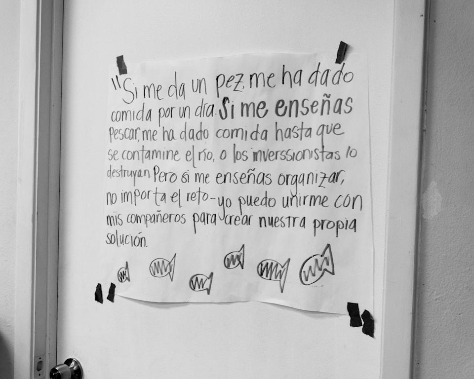 """A sign in the WDP office. """"If you give me a fish, you have given me food for a day. If you teach me to fish, you've given me food until the river becomes contaminated or destroyed by investors. But if you teach me how to organize, regardless of the challenge, I can unite with my community to create our own solution."""""""