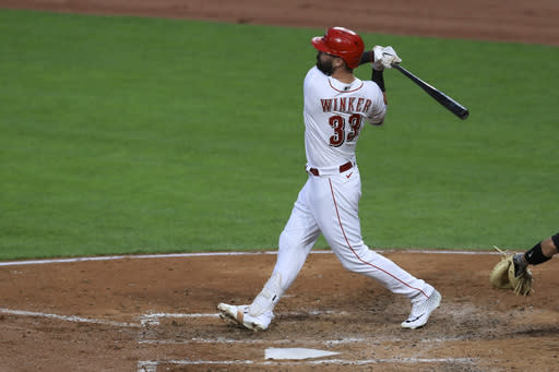 Cincinnati Reds' Jesse Winker hits a two-run home run in the fourth inning during a baseball game against the Pittsburgh Pirates in Cincinnati, Friday, Aug. 14, 2020. (AP Photo/Aaron Doster)