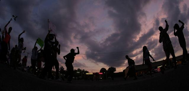 <p>People protest Monday, Aug. 18, 2014, for Michael Brown, who was killed by police Aug. 9 in Ferguson, Mo. (Charlie Riedel/AP) </p>