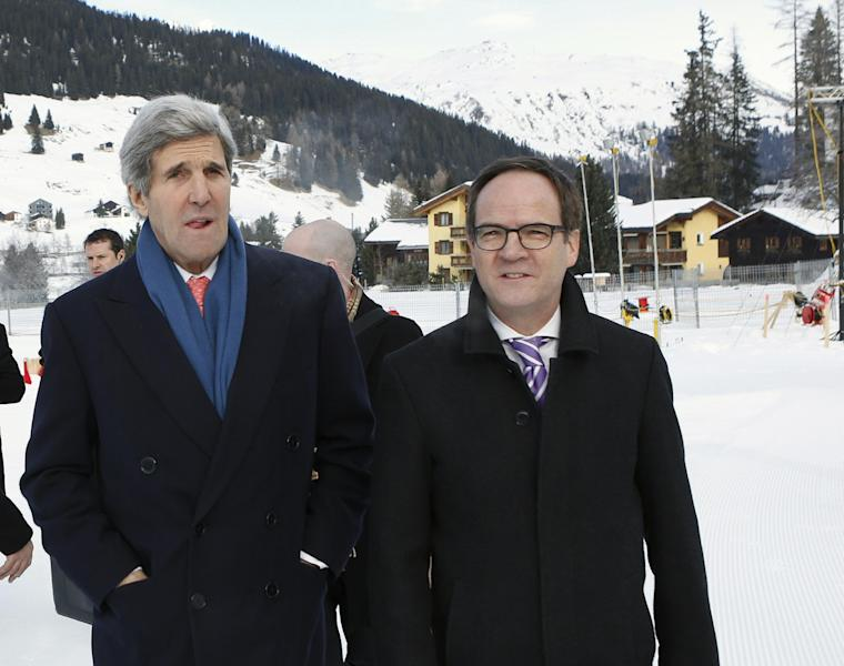 U.S. Secretary of State John Kerry, left, is greeted on his arrival in Davos, Switzerland by Swiss Ambassador Philippe Guex, right, Thursday Jan. 23, 2014, where Kerry will attend the World Economic Forum annual meeting. The UN-backed international conference on the Syrian crisis will continue with separate talks between the rival delegations in Geneva, Switzerland, on upcoming Friday. (AP Photo / Gary Cameron, pool)