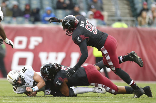 Central Florida quarterback McKenzie Milton (10) is sacked by Temple's Sharif Finch (6) and Quincy Roche (90) during the second quarter of an NCAA college football game Saturday, Nov. 18, 2017, in Philadelphia. (AP Photo/Rich Schultz)