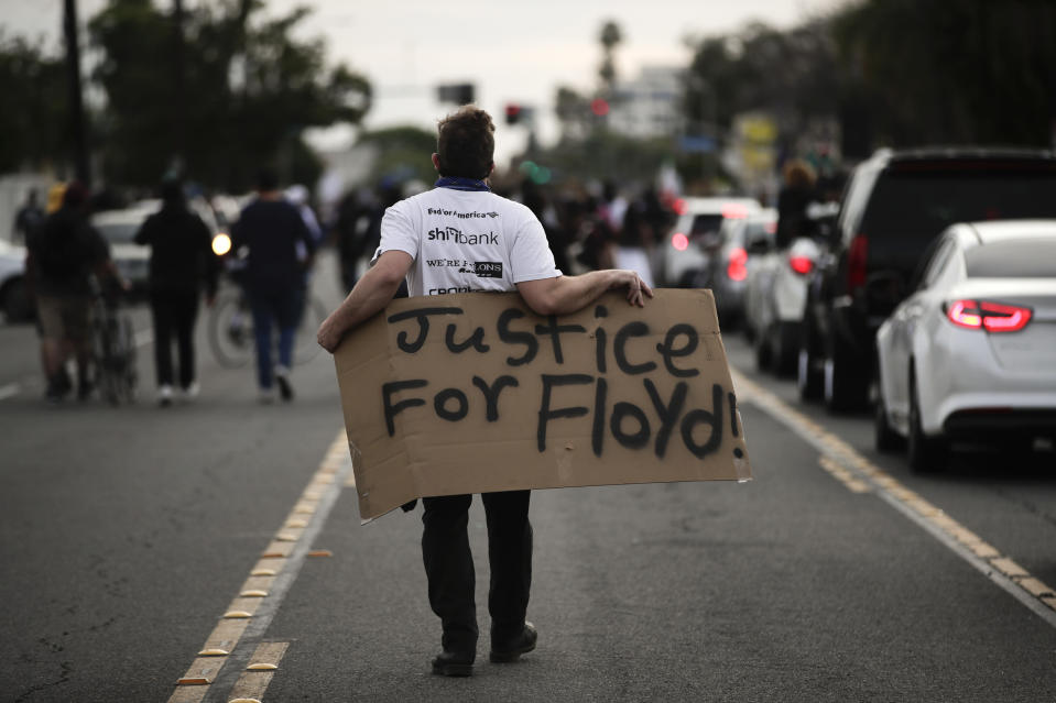 A demonstrator walks with a sign during a protest on Monday in Anaheim, Calif., over the death of George Floyd on May 25 in Minneapolis. (Photo: AP Photo/Jae C. Hong)