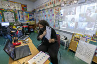 First grade teacher Megan Garner-Jones teaches students participating remotely and in person during the coronavirus outbreak at School 16, Tuesday, Oct. 20, 2020, in Yonkers, N.Y. (AP Photo/Mary Altaffer)
