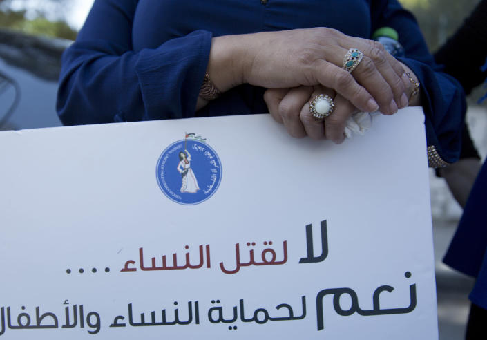 """A Palestinian woman holds a placard that reads """"Palestinian Woman's General Union, no for killing women, yes for protecting women and children,"""" during a rally in front of the Prime Minister's office, in the West Bank city of Ramallah, Monday, Sept. 2. 2019. Hundreds of Palestinian women have protested in front of the prime minister's office to demand an investigation into the death of Israa Ghrayeb, a 21-year-old woman whom many suspect was the victim of a so-called honor killing. (AP Photo/Nasser Nasser)"""