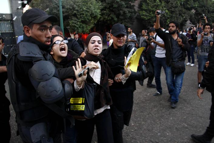 Egyptian police detain two female protesters in Cairo, Tuesday, Nov. 26, 2013, after police water cannons to disperse two protests by dozens of secular anti-government activists, the security forces' first implementation of a controversial new law forbidding protests held without a permit from authorities. (AP Photo/Ahmed Gomaa)