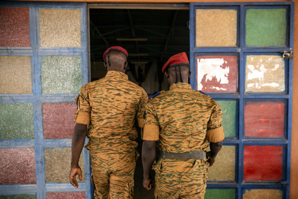 Two soldiers enter the Catholic church at the 10th RCAS army barracks in Kaya, Burkina Faso, Saturday, April 10, 2021. Once considered a beacon of peace and religious coexistence in the region, the West African nation has been embroiled in unprecedented violence linked to al-Qaida and the Islamic State since 2016, throwing an ill-equipped and undertrained army into disarray — and overwhelming the chaplains tasked with supporting them. (AP Photo/Sophie Garcia)