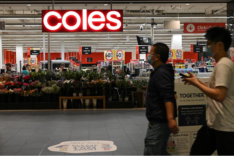 Pictured are two people in face masks walking past a Coles supermarket.
