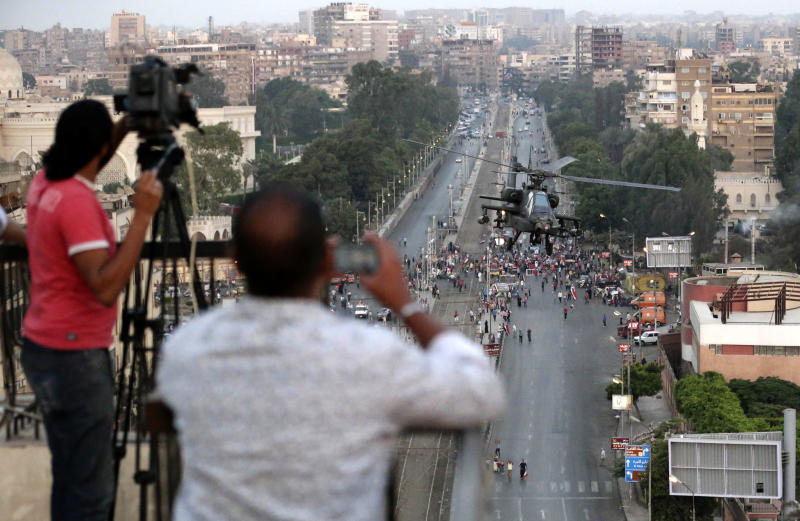 FILE - In this Friday, July 5, 2013 file photo, journalists film an Egyptian military attack helicopter flies by the Presidential palace, in Cairo, Egypt. State-run news organizations and independent TV stations and newspapers have enthusiastically backed the military and its crackdown on the Muslim Brotherhood, which included shutting down four Islamist TV stations. Their full-throated support reflects how convinced they became over President Mohammed Morsi's year that the Brotherhood were fundamentally anti-democratic and intertwined with violent extremists.(AP Photo/Hassan Ammar, File)