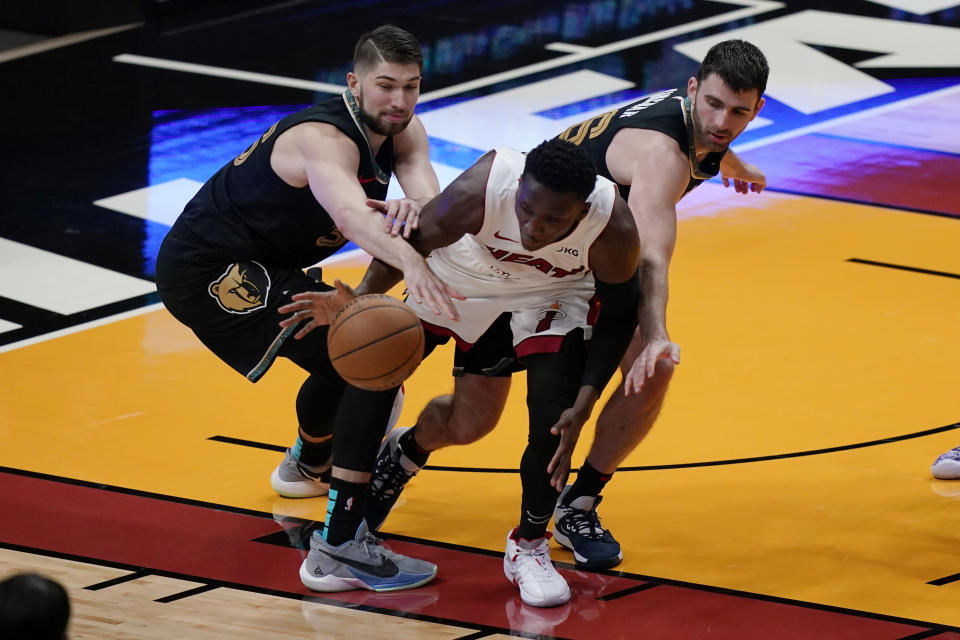 Miami Heat guard Victor Oladipo, middle, and Memphis Grizzlies center Killian Tillie, left, and guard John Konchar (46) go after the ball during the second half of an NBA basketball game Tuesday, April 6, 2021, in Miami. (AP Photo/Marta Lavandier)