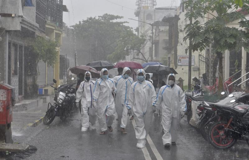 Health care staffs walk on the street of Malvani for the door to door check up at Malad(W) during heavy rain, on July 5, 2020 in Mumbai, India. (Photo by Satyabrata Tripathy/Hindustan Times via Getty Images)