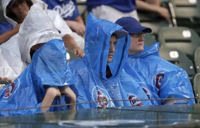 Chicago Cubs fans sit through a rain delay before a baseball game between the Cubs and Los Angeles Dodgers Monday, June 18, 2018, in Chicago. (AP Photo/Charles Rex Arbogast)