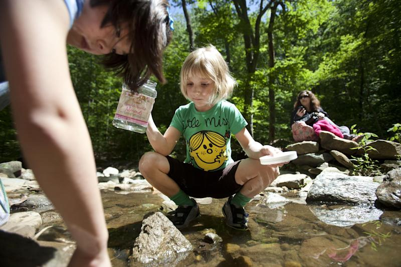 Chloe Moskowitz, 7, of Vienna, Va., left, and Lori Anne Madison, 6, of Lake Ridge, Va., hunt for tadpoles, with Lori Anne Madison's mother Sorina V. Madison, right, in McLean, Va., on Friday, May 11, 2012. Lori Anne is the youngest contestant in the 2012 National Spelling Bee. (AP Photo/Jacquelyn Martin)