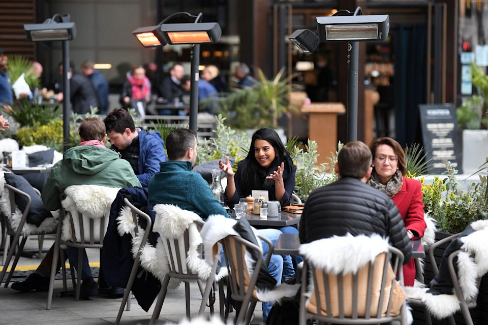 People eat and drink while sitting at tables outside a restaurant at lunchtime in the City of London on April 29, 2021. - Britain has been the European country worst-hit by the virus, recording more than 127,000 deaths, although it rolled out a succesful mass-vaccination campaign in early December, using AstraZeneca, Pfizer/BioNTech and Moderna vaccines. (Photo by DANIEL LEAL-OLIVAS / AFP) (Photo by DANIEL LEAL-OLIVAS/AFP via Getty Images)