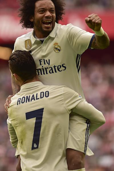 Real Madrid's Cristiano Ronaldo, celebrates with Marcelo Vieira, top, after their team scored during the Spanish La Liga soccer match between Real Madrid and Athletic Bilbao, at San Mames stadium, in Bilbao, northern Spain, Saturday, March 18, 2017. (AP Photo/Alvaro Barrientos)