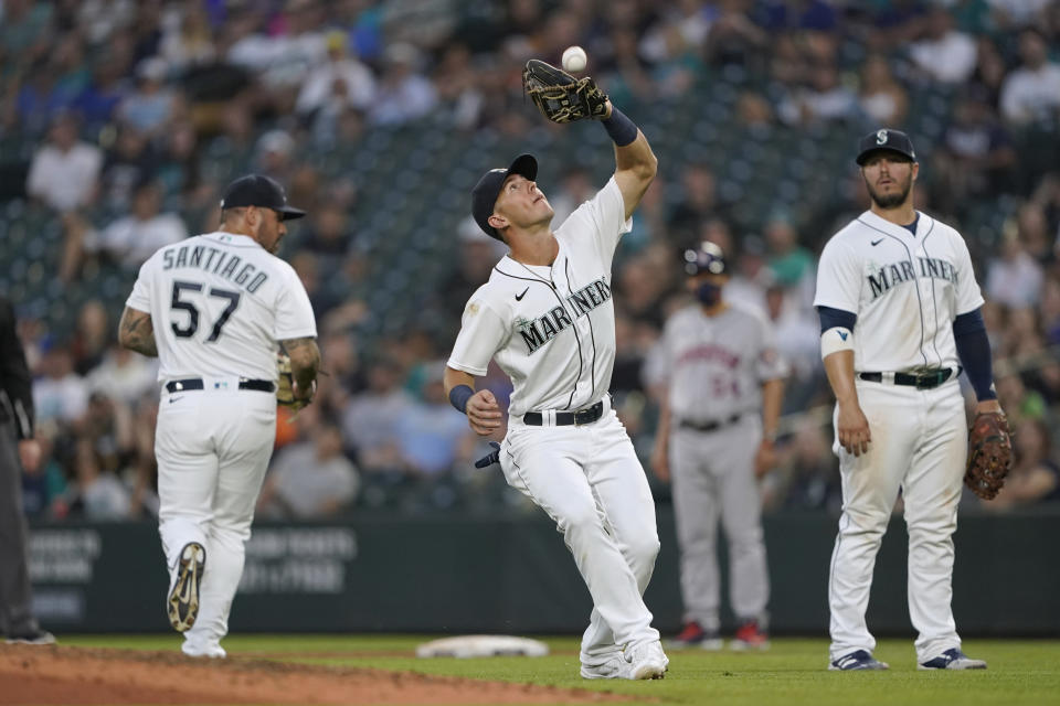 Seattle Mariners shortstop Dylan Moore, center, catches a popup hit by Houston Astros' Carlos Correa during the fifth inning of a baseball game Tuesday, July 27, 2021, in Seattle. (AP Photo/Ted S. Warren)