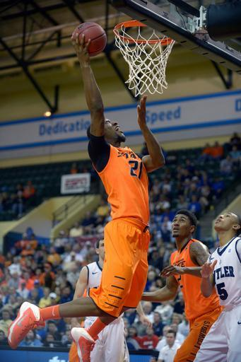 Oklahoma State forward Kamari Murphy (21) puts up a shot over Le'Bryan Nash (2) and Butler guard Elijah Brown (5) during the first half of an NCAA college basketball game at the Old Spice Classic tournament in Kissimmee, Fla., Friday, Nov. 29, 2013. (AP Photo/Phelan M. Ebenhack)