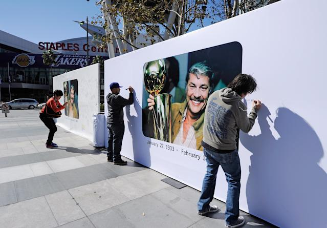 LOS ANGELES, CA - FEBRUARY 20: Lakers fan Mike Delahaut (R) writes a personal message on the Dr. Buss Memorial Banners in the Nokia Plaza at L.A. Live, directly across the street from Staples Center on February 20, 2013 in Los Angeles, California. The Lakers will hold a memorial service to celebrate the life of longtime owner Jerry Buss at the Nokia Theater on Thursday, for invited guests only. Dr. Buss died at the age of 80 on Monday following an 18-month battle with cancer. (Photo by Kevork Djansezian/Getty Images)