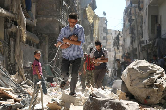 Survivors of a reported air strike a section of Aleppo