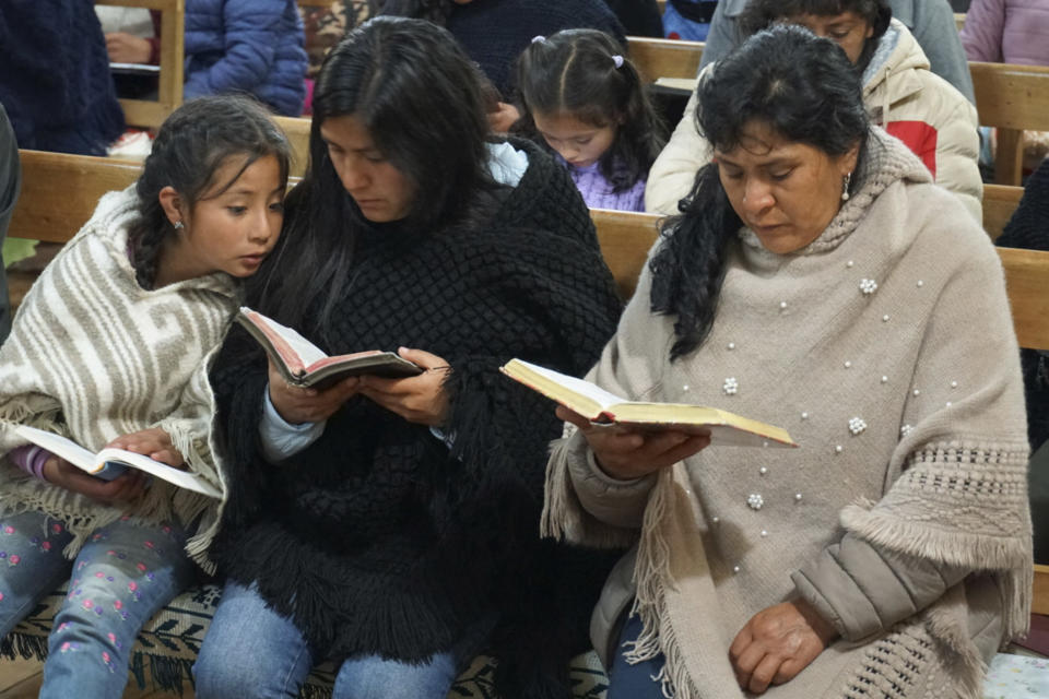 Peru's future first lady Lilia Paredes, right, reads from the Bible while sitting next to her younger sister Yenifer, and her 9-year-old daughter Alondra, during a church service in which neighbors were invited to say goodbye before the family's departure to Lima, at the Nazarene church in Chugur, Peru, Thursday, July 22, 2021. Her husband, leftist Pedro Castillo catapulted from unknown to president-elect with the support of the country's poor and rural citizens, many of whom identify with the struggles the teacher has faced. (AP Photo/Franklin Briceno)