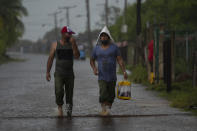 People walk down a street flooded by the rains brought on by Hurricane Ida, in Guanimar, Artemisa province, Cuba, Saturday, Aug. 28, 2021. (AP Photo/Ramon Espinosa)